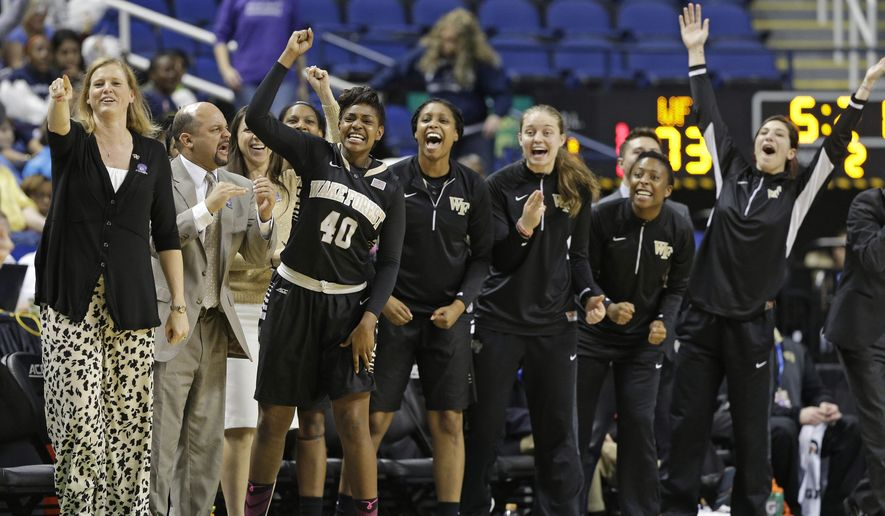 The Wake Forest bench, including Wake Forest head coach Jen Hoover, left, cheer after a teammate's basket against Syracuse during the second half of an Atlantic Coast Conference women's tournament basketball game in Greensboro, N.C., Thursday, March 5, 2015. Wake Forest won 85-79. (AP Photo/Chuck Burton)