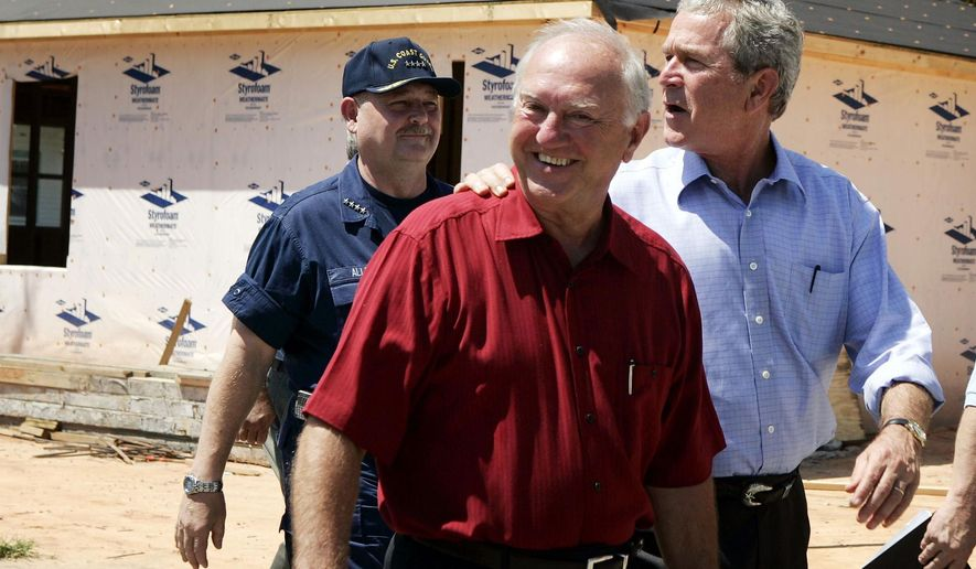 FILE - In this Aug. 28, 2006, file photo, President Bush, right, takes a tour of a neighborhood damaged by Hurricane Katrina with Biloxi, Miss., Mayor A.J. Holloway, center, in Biloxi. Holloway, who had already temporarily left his post on Jan. 29, 2015, to enter an alcohol rehabilitation facility, will resign Tuesday, March 10. (AP Photo/Evan Vucci, File)