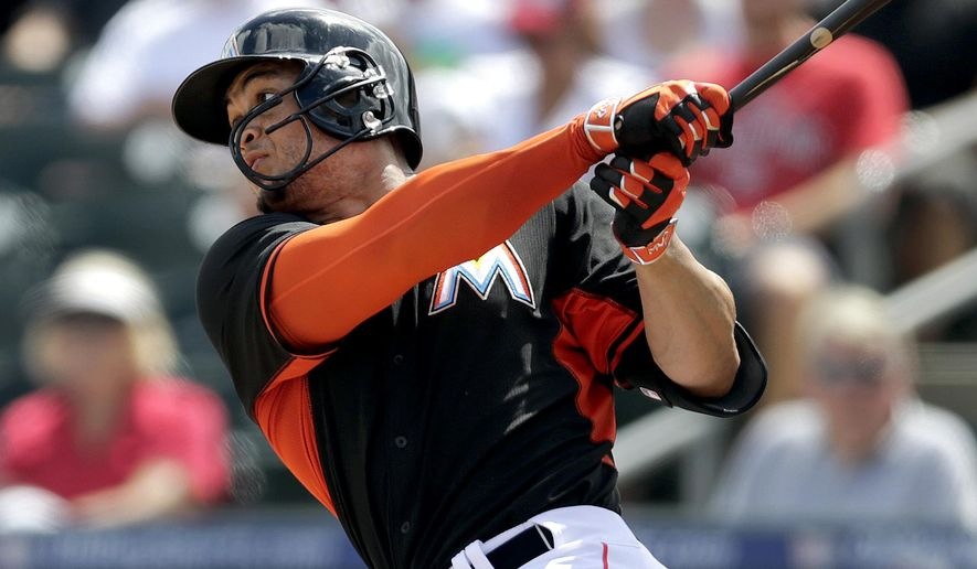 Miami Marlins' Giancarlo Stanton flies out during the first inning of an exhibition spring training baseball game against the St. Louis Cardinals Thursday, March 5, 2015, in Jupiter, Fla. Stanton is wearing a newly designed helmet this season featuring a half-facemask to protect the left side of his face after he broke his orbital bone and damaged five teeth while being hit by a pitch ending his 2014 season. (AP Photo/Jeff Roberson)