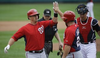 Washington Nationals' Tyler Moore, left, is high-fived by teammate Dan Uggla after Uggla scored off of Moore's two-run home run in the second inning of an exhibition spring training baseball game against the Atlanta Braves, Friday, March 6, 2015, in Kissimmee, Fla. (AP Photo/David Goldman)