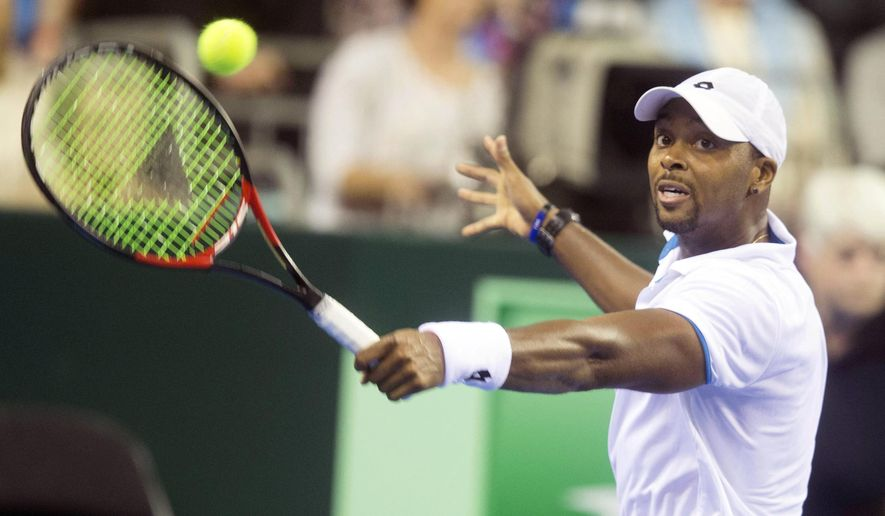 Donald Young of the US returns the ball to Britain's Andy Murray during the first round Davis Cup match between Britain and US at the Emirates Arena in Glasgow, Friday March 6, 2015. (AP Photo/PA, Jeff Holmes) UNITED KINGDOM OUT  NO SALES  NO ARCHIVE