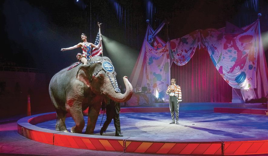FILE - In this photo taken on Thursday, Feb. 19, 2015, ringmaster Andre McClain, center, holds his hat to his heart as the national anthem is played during the opening of the Ringling Brothers and Barnum & Bailey Circus, at Knoxville Civic Coliseum, Knoxville, Tenn.  The circus will phase out the show's iconic elephants from its performances by 2018, telling The Associated Press exclusively on Thursday, March 5, 2015 that growing public concern about how the animals are treated led to the decision. (AP Photo/The Daily Times, Mark A. Large) MANDATORY CREDIT