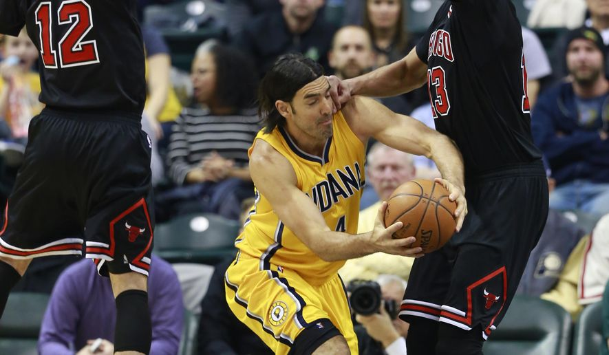 Chicago Bulls guard Kirk Hinrich (12) and center Joakim Noah, right, keep Indiana Pacers forward Luis Scola from advancing the basketball in the first half of an NBA basketball game, Friday, March 6, 2015, in Indianapolis. (AP Photo/R Brent Smith)