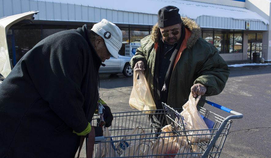 """Shelley Haywood, left, and Thomas Stanton, right, load their groceries into the car on Wednesday, March 4, 2015, after shopping at the Davision Road Kroger in Flint, Mich.  Kroger officials confirmed the closing of the company's store at the end of the month  Haywood expressed grave sadness about """"having to watch so many stores close"""" in and around her neighborhood. Public transit officials in Flint plan to adjust bus routes to ensure that residents have easier access to fresh food following the planned shutdown of some big grocery stores in the area.  (AP Photo/The Flint Journal-MLive.com, Sam Owens) LOCAL TELEVISION OUT; LOCAL INTERNET OUT"""