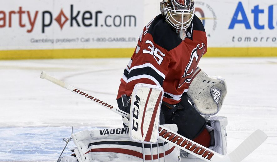 New Jersey Devils goaltender Cory Schneider deflects the puck during the first period of an NHL hockey game against the Columbus Blue Jackets on Friday, March 6, 2015, in Newark, N.J. (AP Photo/Bill Kostroun)