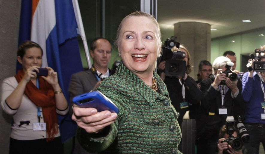 FILE - In this Dec. 8, 2011, file photo, then-U.S. Secretary of State Hillary Rodham Clinton hands off her mobile phone after arriving to meet with Dutch Foreign Minister Uri Rosenthal at the Ministry of Foreign Affairs in The Hague, Netherlands. The personal email server used by Clinton during her time as secretary of state was probably about the size of your office desktop computer. Setting up your own email server is easier and cheaper than you might think. (AP Photo/J. Scott Applewhite, Pool/File)