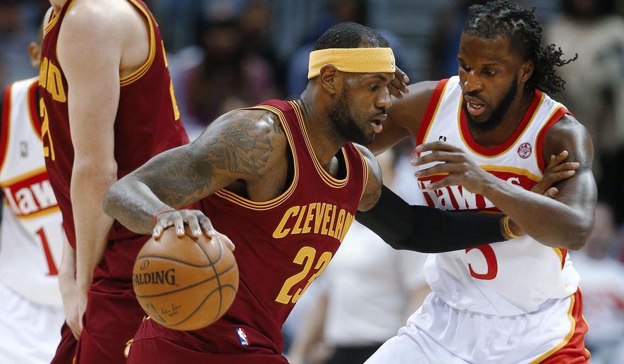 Cleveland Cavaliers forward LeBron James (23) drives against Atlanta Hawks forward DeMarre Carroll (5) during the first half of an NBA basketball game Friday, March 6, 2015, in Atlanta. (AP Photo/John Bazemore)