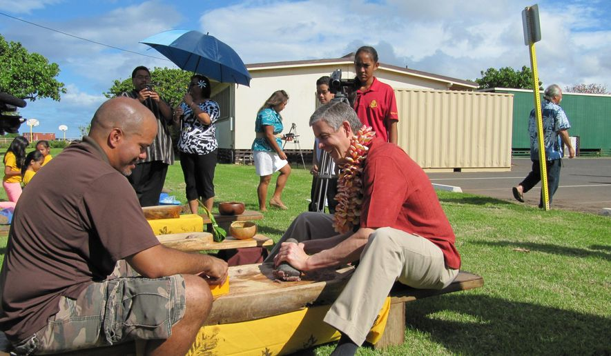 FILE - In this March 31, 2014 file photo, U.S. Education Secretary Arne Duncan, right, gets a lesson in making the Hawaiian food staple poi from Kelii Marrotte, a fourth-grade teacher at Ka Waihona o ka Naauao Public Charter School in Waianae, Hawaii. Hawaii is one of only a handful of states that received a flawless progress report on promised reforms to replace provisions of the federal No Child Left Behind education law.(AP Photo/Jennifer Sinco Kelleher, file)