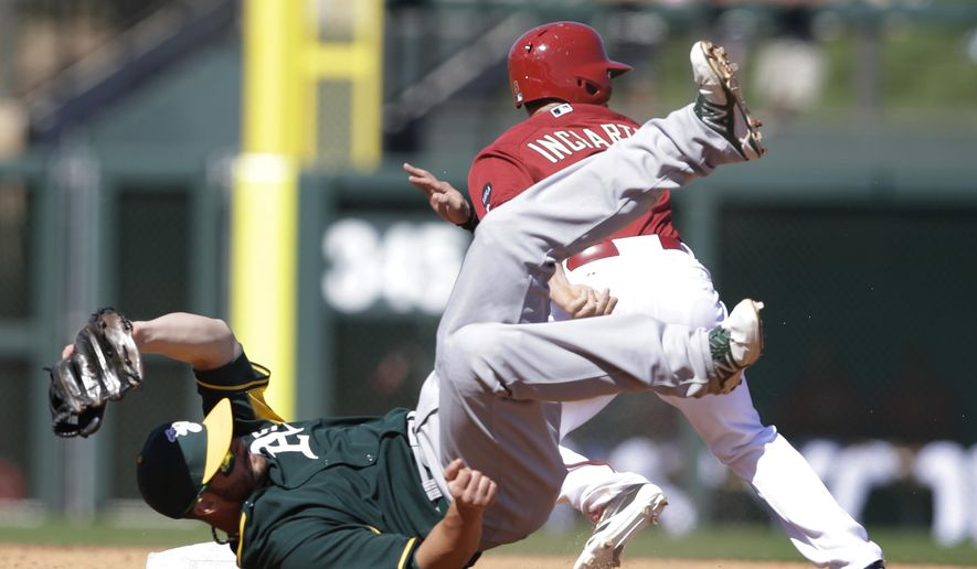 Oakland Athletics' Andy Parrino falls down after trying to catch a throw as Arizona Diamondbacks' Ender Inciarte (5) steals second during the third inning of a spring training baseball game Friday, March 6, 2015, in Scottsdale, Ariz. Inciarte advanced to third on a throwing error by catcher Josh Phegley. (AP Photo/Darron Cummings)