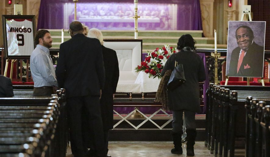 "Mourners pass by the casket of former Chicago White Sox great Minnie Minoso on Friday, March 6, 2015, to pay their respects during a public visitation at Holy Family Church in Chicago.  The Havana native and major league baseball's first black Latino star died Sunday, March 1. He was believed to be 90. Known as the ""Cuban Comet,"" Minoso was part of a wave of black players who transformed the game. (AP Photo/M. Spencer Green)"