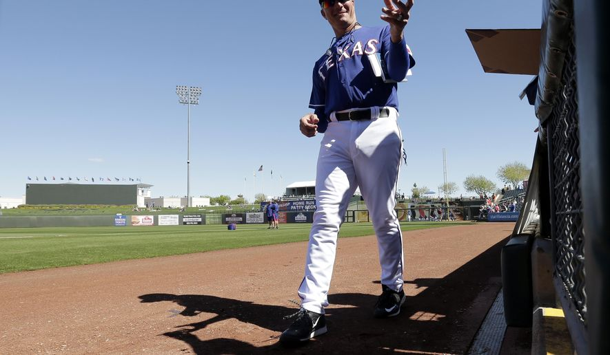 Texas Rangers manager Jeff Banister signs autographs before a spring training baseball game against the Kansas City Royals, Wednesday, March 4, 2015, in Surprise, Ariz. (AP Photo/Charlie Riedel)