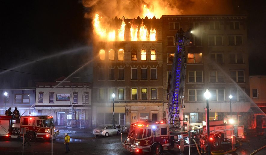 Schenectady firefighters battle a blaze that gutted two five-story apartment buildings early Friday, March 6, 2015, in Schenectady, N.Y. At least seven people were injured, including a man who jumped from a top floor, authorities said. (AP Photo/The Daily Gazette, Peter R. Barber)  TROY, SCHENECTADY; SARATOGA SPRINGS; ALBANY AND AMSTERDAM OUT