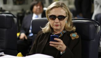 In this 2011 photo, then-Secretary of State Hillary Rodham Clinton checks her Blackberry from a desk inside a C-17 military plane en route to Tripoli, Libya. (AP Photo/Kevin Lamarque, Pool, File)