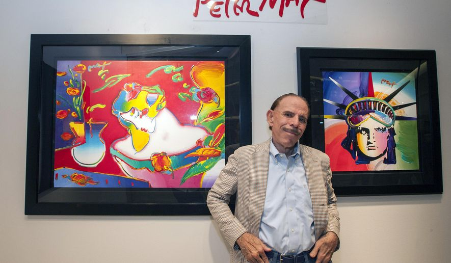 FILE - In this Sept. 6, 2014, file photo, artist Peter Max poses for a photo during his retrospective with the Road Show Company exhibit in Northbrook Court mall in Northbrook, Ill. Since he charged onto the pop-art stage a half-century ago, the progenitor of psychedelic art has stamped his creative presence on practically everything from the sides of an airliner and the hull of a Norwegian Cruise Lines ship to commemorative U.S. postage stamps and, most lately, an endless string of art galleries stretching from one end of the United States to the other. (Photo by Barry Brecheisen/Invision/AP, File)