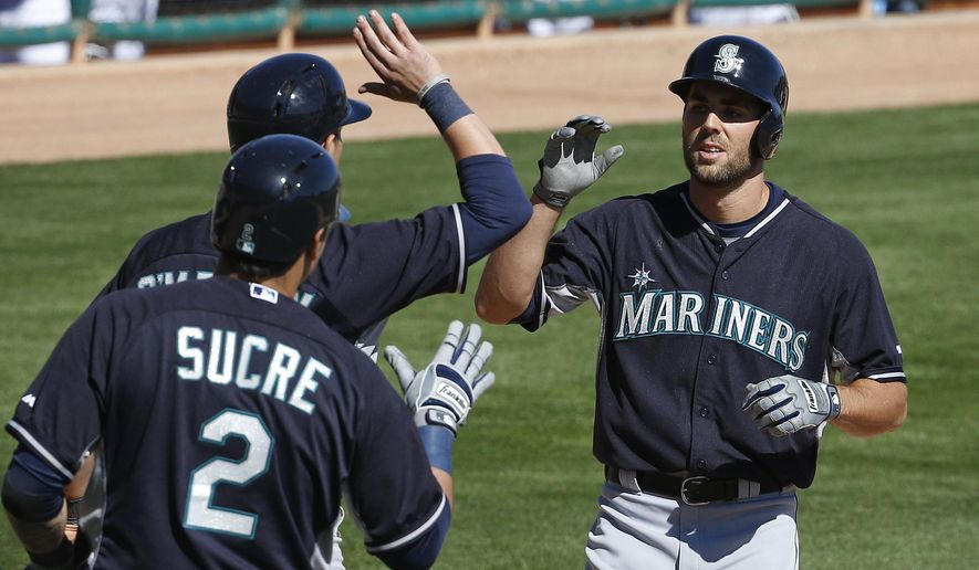 Seattle Mariners' Chris Taylor, right, is congratulated by teammates Jesus Sucre (2) and Shawn O'Malley as Taylor crosses home plate after hitting a home run in the fifth inning of a spring training exhibition baseball game against Los Angeles Dodgers, Friday, March 6, 2015, in Phoenix. (AP Photo/John Locher)