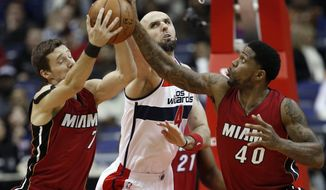 Miami Heat guard Goran Dragic (7), from Slovenia, Washington Wizards center Marcin Gortat (4), from Poland, and forward Udonis Haslem (40) go for a rebound in the first half of an NBA basketball game Friday, March 6, 2015, in Washington. (AP Photo/Alex Brandon)