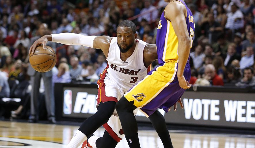 Miami Heat's Dwyane Wade (3) drives to the basket against Los Angeles Lakers' Jordan Clarkson (6) during the second half of an NBA basketball game in Miami, Wednesday, March 4, 2015. The Heat defeated the Lakers 100-94. (AP Photo/Joel Auerbach)