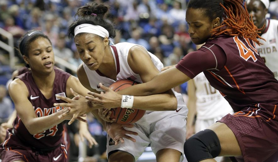 Florida State's Ivey Slaughter, center, is trapped by Virginia Tech's Rachel Camp, left, and Dominique Powell, right, during the first half of an NCAA college basketball game in the quarterfinals of the Atlantic Coast Conference women's tournament in Greensboro, N.C., Friday, March 6, 2015. (AP Photo/Chuck Burton)