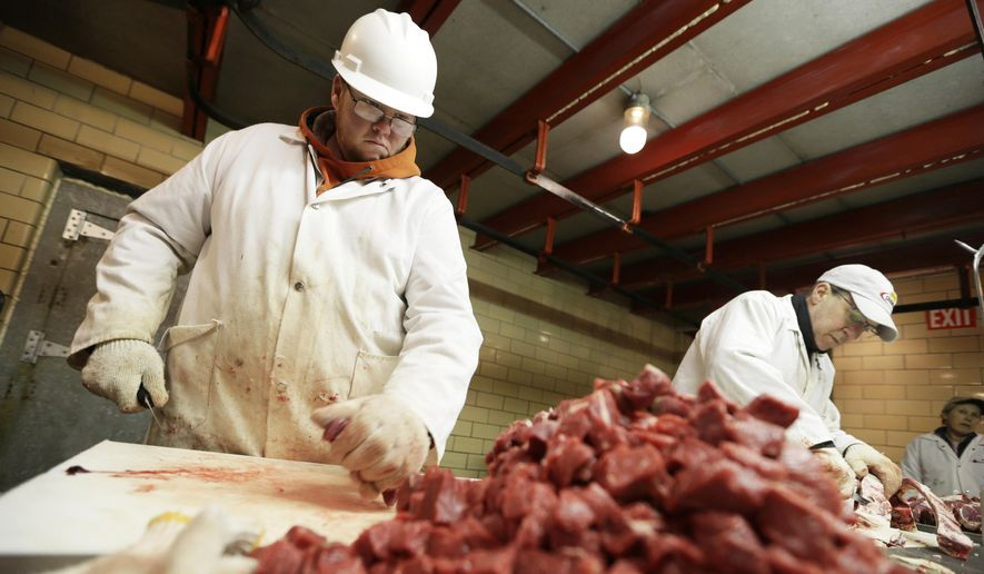 Amend Packing Co. worker Chris Jorgensen, left, cuts stew meat, Tuesday, Feb. 17, 2015, in Des Moines, Iowa. (AP Photo/Charlie Neibergall)