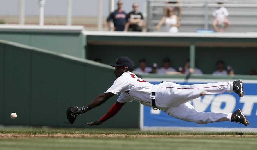 Boston Red Sox second baseman Jemile Weeks dives, but is unable to reach a single by Miami Marlins' Marcell Ozuna, in the first inning of a spring training baseball game in Fort Myers Fla., March 6, 2015. (AP Photo/Tony Gutierrez)