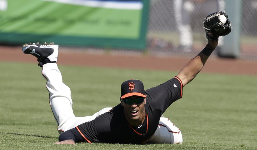 San Francisco Giants' Justin Maxwell (43) makes a diving catch on a ball hit by Chicago Cubs' Chris Valaika during the fourth inning of a spring training baseball game Thursday, March 5, 2015, in Scottsdale, Ariz. (AP Photo/Darron Cummings)