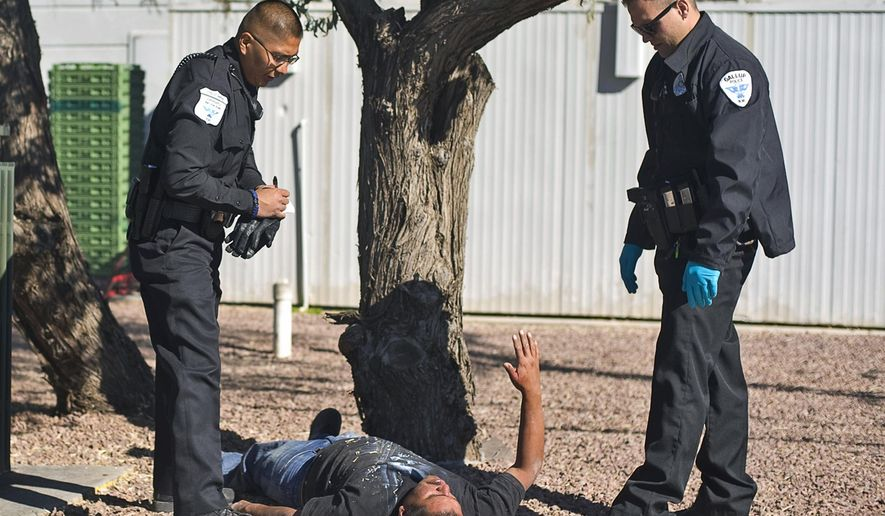In this October 2012 photo, Gallup, N.M. Community Service Aide Timothy Hughte, left, and police officer Matthew Graham check on a man who had passed out in a restaurant parking lot in Gallup. In a state with some of the highest rates of suicide, mental illness and substance abuse-related deaths, legislation targeting high-risk areas with more money and treatment programs proven to work is winning bipartisan support. A bill that would establish behavioral health investment zones across New Mexico has passed the House on a 62-1 vote Tuesday, March 3, 2015, and is now pending in the Senate. (AP Photo/Gallup Independent, Brian Leddy)