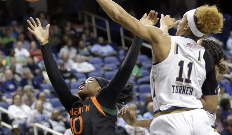 Miami's Michelle Woods (10) shoots past Notre Dame's Brianna Turner (11) during the first half of an NCAA college basketball game in the quarterfinals of the Atlantic Coast Conference women's tournament in Greensboro, N.C., Friday, March 6, 2015. (AP Photo/Chuck Burton)