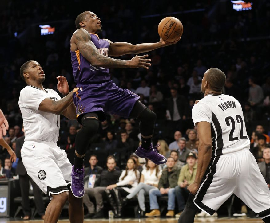 Phoenix Suns' Eric Bledsoe, center, drives past Brooklyn Nets' Joe Johnson, left, and Markel Brown, right, during the first half of an NBA basketball game Friday, March 6, 2015, in New York. (AP Photo/Frank Franklin II)