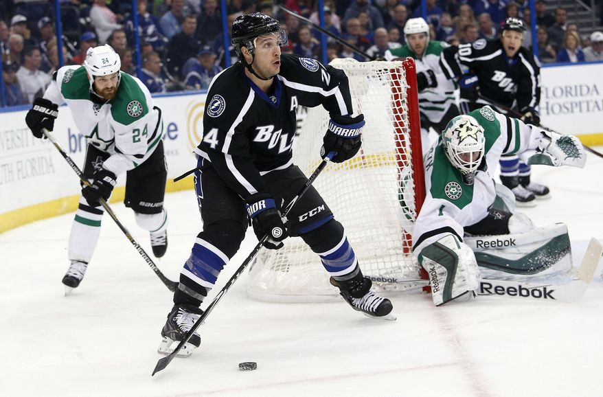 Tampa Bay Lightning right wing Ryan Callahan (24) controls the puck between Dallas Stars defenseman Jordie Benn (24) and goalie Jhonas Enroth (1) during the second period of an NHL hockey game Saturday, March 7, 2015, in Tampa, Fla. (AP Photo/Brian Blanco)