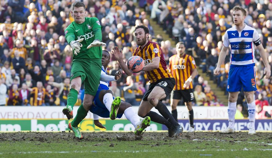 Reading's Yakubu, second left, fights for the ball against Bradford's goalkeeper Ben Williams, left, and Rory McArdle, centre, as Alex Pearce, right, looks on looks on during their English FA Cup quarter final soccer match at Valley Parade Stadium, Bradford, England, Saturday March 7, 2015. (AP Photo/Jon Super)