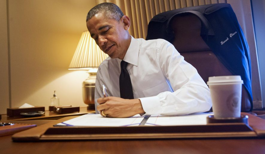 """President Barack Obama signs legislation awarding a Congressional Gold Medal to the people who participated in the """"Bloody Sunday"""" march, Turnaround Tuesday, or the final Selma to Montgomery Voting Rights March in March of 1965, at his desk aboard Air Force One Saturday, March 7, 2015. The president was en route to Selma, Ala., to attend the 50th Anniversary of """"Bloody Sunday,"""" which refers to the day in 1965 when police attacked marchers demonstrating for voting rights. (AP Photo/Jacquelyn Martin)"""