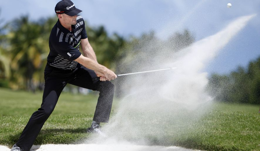 James Driscoll of the U.S. hits the ball out of the bunker on the 18th hole during the third round of the Puerto Rico Open PGA golf tournament in Rio Grande, Puerto Rico, Saturday, March 7, 2015. (AP Photo/Ricardo Arduengo)