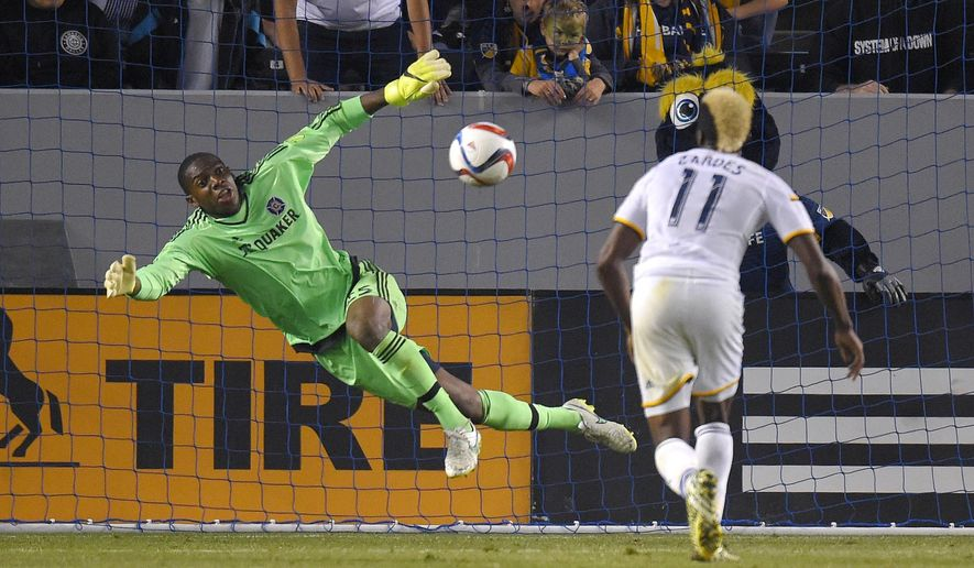 Chicago Fire goalkeeper Sean Johnson, left, dives to stop a shot as Los Angeles Galaxy forward Gyasi Zardes watches during the first half of an MLS soccer match, Friday, March 6, 2015, in Los Angeles. (AP Photo/Mark J. Terrill)
