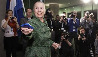 In this Dec. 8, 2011, file photo, then-U.S. Secretary of State Hillary Rodham Clinton hands off her mobile phone after arriving to meet with Dutch Foreign Minister Uri Rosenthal at the Ministry of Foreign Affairs in The Hague, Netherlands. Clinton is far from alone in using her private email account to conduct official business. In state capitals around the country, governors and other elected officials routinely use private emails, laptops and cell phones in their jobs, a popular strategy to avoid public scrutiny of their actions. (AP Photo/J. Scott Applewhite, Pool/File)