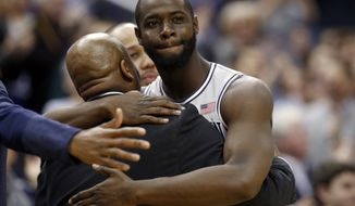Georgetown center Tyler Adams, right, is hugged by head coach John Thompson III after coming out of the game during the first half of an NCAA college basketball game against Seton Hall, Saturday, March 7, 2015, in Washington. Adams started, and hasn't played in a game since 2011, sidelined because of a heart ailment. (AP Photo/Alex Brandon)
