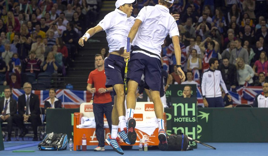 Mike Bryan (left) and Bob Bryan of the U.S celebrate a point against Britain's Dominic Inglot and Jamie Murray during their Davis Cup tennis doubles match at the Emirates Arena, Glasgow, Scotland, Saturday, March 7, 2015. (AP Photo/Jeff Holmes, PA Wire)      UNITED KINGDOM OUT     -     NO SALES     -    NO ARCHIVES