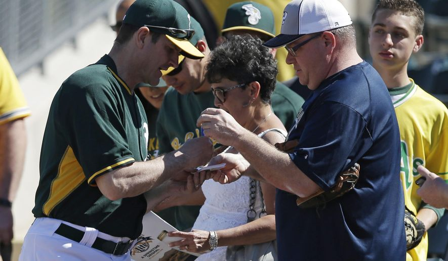 Michigan football coach Jim Harbaugh,left, signs autographs before a spring training baseball game between the Oakland Athletics and Los Angeles Angels, Saturday, March 7, 2015, in Mesa, Ariz. (AP Photo/Darron Cummings)