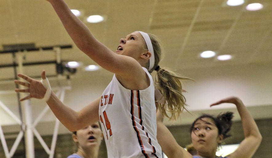 Princeton Tigers guard Amanda Berntsen (14) goes up past Columbia Lions guard Miwa Tachibana (00) and forward Camille Zimmerman (20) during the first half of an NCAA college basketball game, Saturday, March 7, 2015, in New York. (AP Photo/Mary Altaffer)