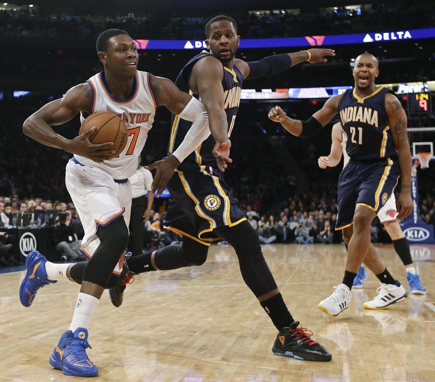 New York Knicks' Cleanthony Early (17) drives past Indiana Pacers' C.J. Miles and David West (21) during the first half of an NBA basketball game Saturday, March 7, 2015, in New York. (AP Photo/Frank Franklin II)