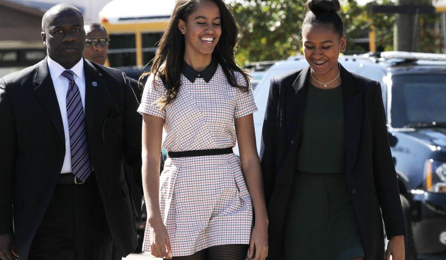 """Malia Obama, left, and sister Sasha Obama laugh together as they leave a speech by their father President Barack Obama at the Edmund Pettus Bridge in Selma, Ala., on the 50th anniversary of """"Bloody Sunday,"""" a landmark event of the civil rights movement, Saturday, March 7, 2015.  (AP Photo/Jacquelyn Martin)"""