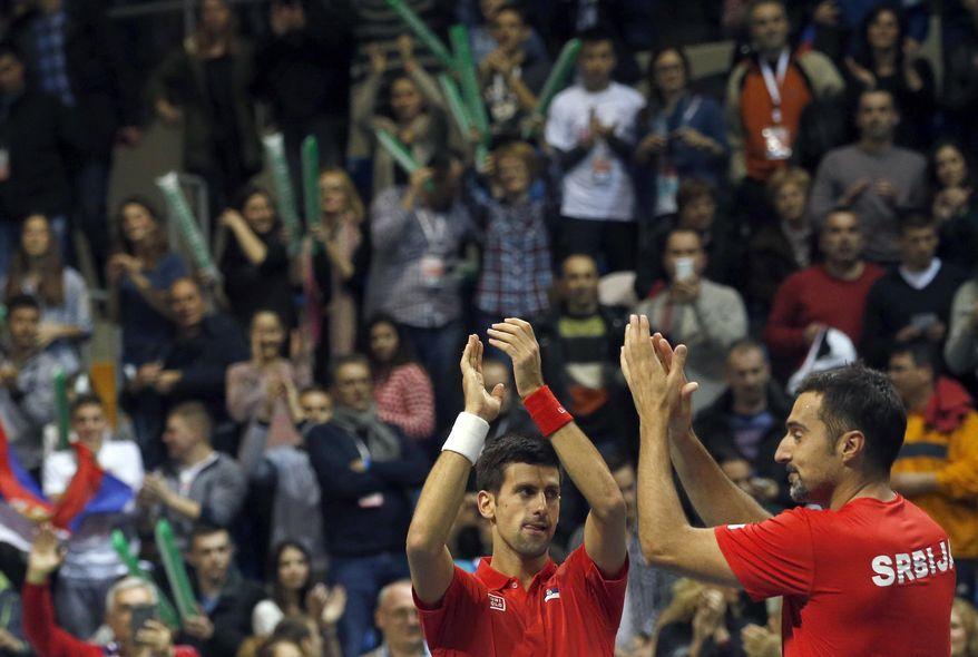 Serbia's Novak Djokovic, center and his partner Nenad Zimonjic celebrate after they won their Davis Cup World Group first round doubles tennis match against Croatia's Marin Draganja and Franko Skugor, in Kraljevo, Serbia, Saturday, March 7, 2015. Zimonjic and Djokovic won the match and gave Serbia a 3-0 lead. (AP Photo/Darko Vojinovic)