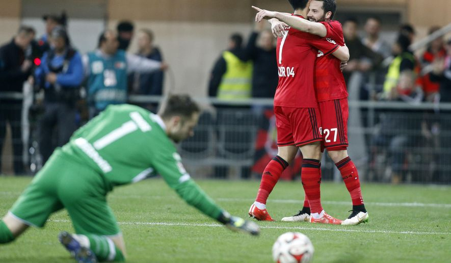 Leverkusen's Gonzalo Castro, right, and Leverkusen's Son Heung-min from South Korea , center, celebrate after scoring  during the German first division Bundesliga soccer match between SC Paderborn and Bayer 04 Leverkusen in Paderborn, Germany, Sunday, March 8, 2015. (AP Photo/Frank Augstein)