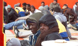 ANOTHER WAVE: Migrants are being rescued in the harbor of the island of Lampedusa, Italy. With Libya's security rapidly deteriorating, the number of people setting out in smugglers' boats to cross the Mediterranean Sea toward Italy has surged. (Associated Press)
