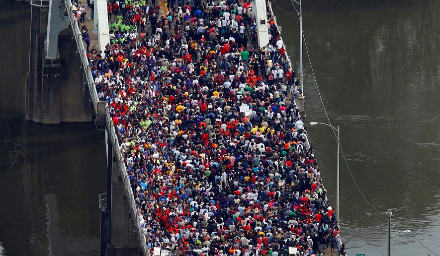 "Crowds moved in a symbolic walk across the Edmund Pettus Bridge on Sunday in Selma, Alabama, where 50 years ago civil rights protesters were beaten, trampled and tear-gassed by police in what was termed ""Bloody Sunday."" Attending ceremonies this weekend were President Obama, former President George W. Bush and their wives, but no Republican presidential prospect in next year's elections. (Associated Press)"