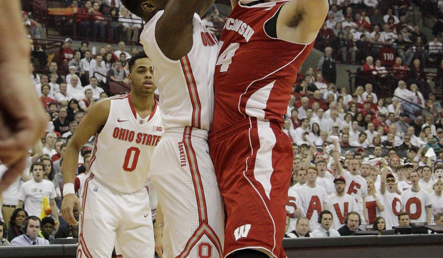 Wisconsin's Frank Kaminsky, right, tries to shoot over Ohio State's Jai'Sean Tate during the first half of an NCAA college basketball game Sunday, March 8, 2015, in Columbus, Ohio. (AP Photo/Jay LaPrete)