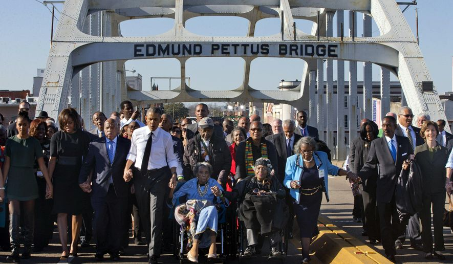 "President Barack Obama, fourth from left, walks holding hands with Amelia Boynton Robinson, who was beaten during ""Bloody Sunday,"" as they and the first family and others including Rep. John Lewis, D-Ga, left of Obama, walk across the Edmund Pettus Bridge in Selma, Ala,. for the 50th anniversary of the landmark event of the civil rights movement, Saturday, March 7, 2015. At far left is Sasha Obama and at far right is former first lady Laura Bush. Adelaide Sanford also sits in a wheelchair. (AP Photo/Jacquelyn Martin) ** FILE **"