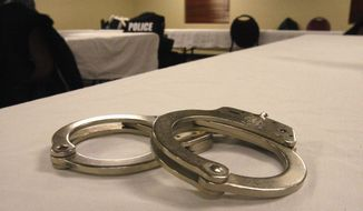 Handcuffs lay on a table in this file photo from March 2015. A First Amendment group is springing into action after reports that two UConn students were arrested essentially for having shouted racist epithets in public, a violation of their free speech rights, according to the Foundation for Individual Rights in Education. (AP Photo/Martha Irvine) **FILE**