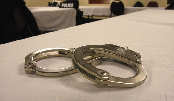 Handcuffs used on men arrested for prostitution solicitation sit on a table at a hotel in Minot, N.D., on Saturday, Jan. 31, 2015. Sex trafficking has become a big problem in North Dakota amid an oil boom that has brought in money and oil workers. The Minot police sting ended with the arrests of 13 men, who answered ads on an escort website posted by the undercover officers. (AP Photo/Martha Irvine)