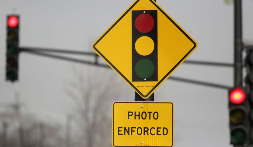 A sign warns motorists of the presence of a red light camera in Chicago. Chicago Mayor Rahm Emanuel's administration on Sunday, March 8, 2015 announced 50 controversial red-light cameras will be taken down from about two dozen locations citywide. The move comes as the former White House chief of staff seeks re-election and faces questions about the cameras impact on safety. (AP Photo/M. Spencer Green, File)
