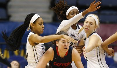 Dayton guard Kelley Austria, center, looks for help as George Washington guard Alexis Chandler, left,  forward Jonquel Jones, top center, and forward Kelli Prange, right, defend during the first half of the Atlantic 10 Championship NCAA college basketball game in Richmond, Va., Sunday, March 8, 2015. (AP Photo/ Steve Helber)